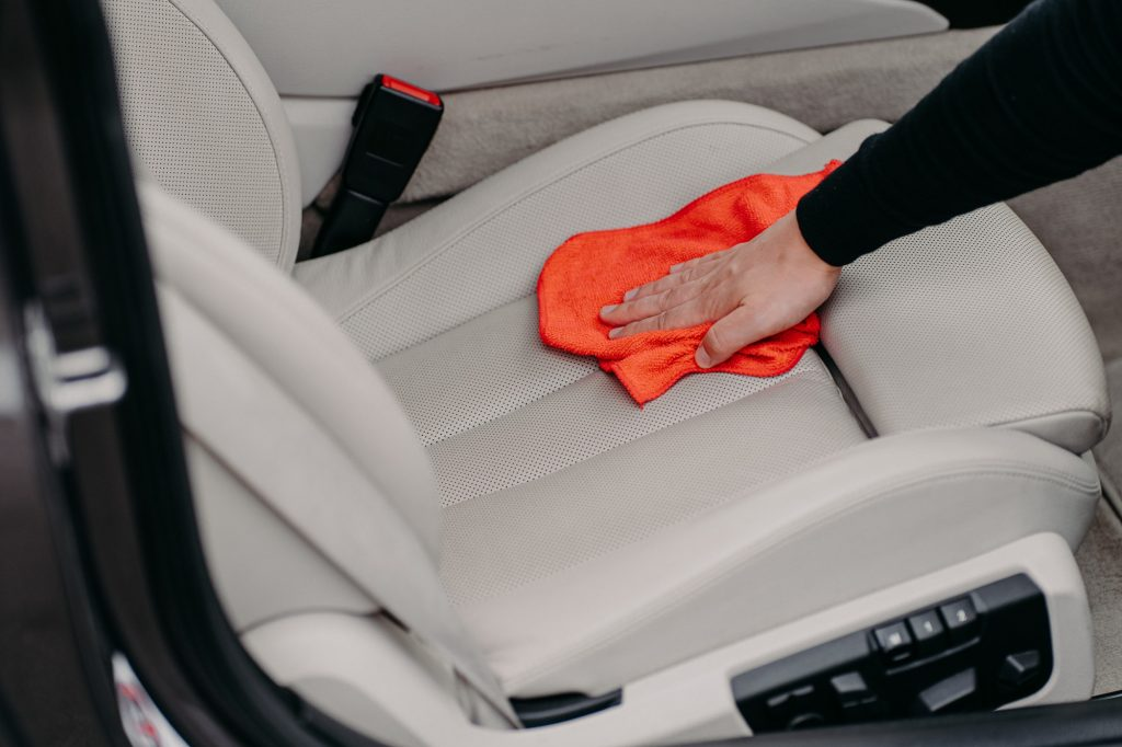 Close up shot of male worker cleans seat inside of car using microfibre cloth