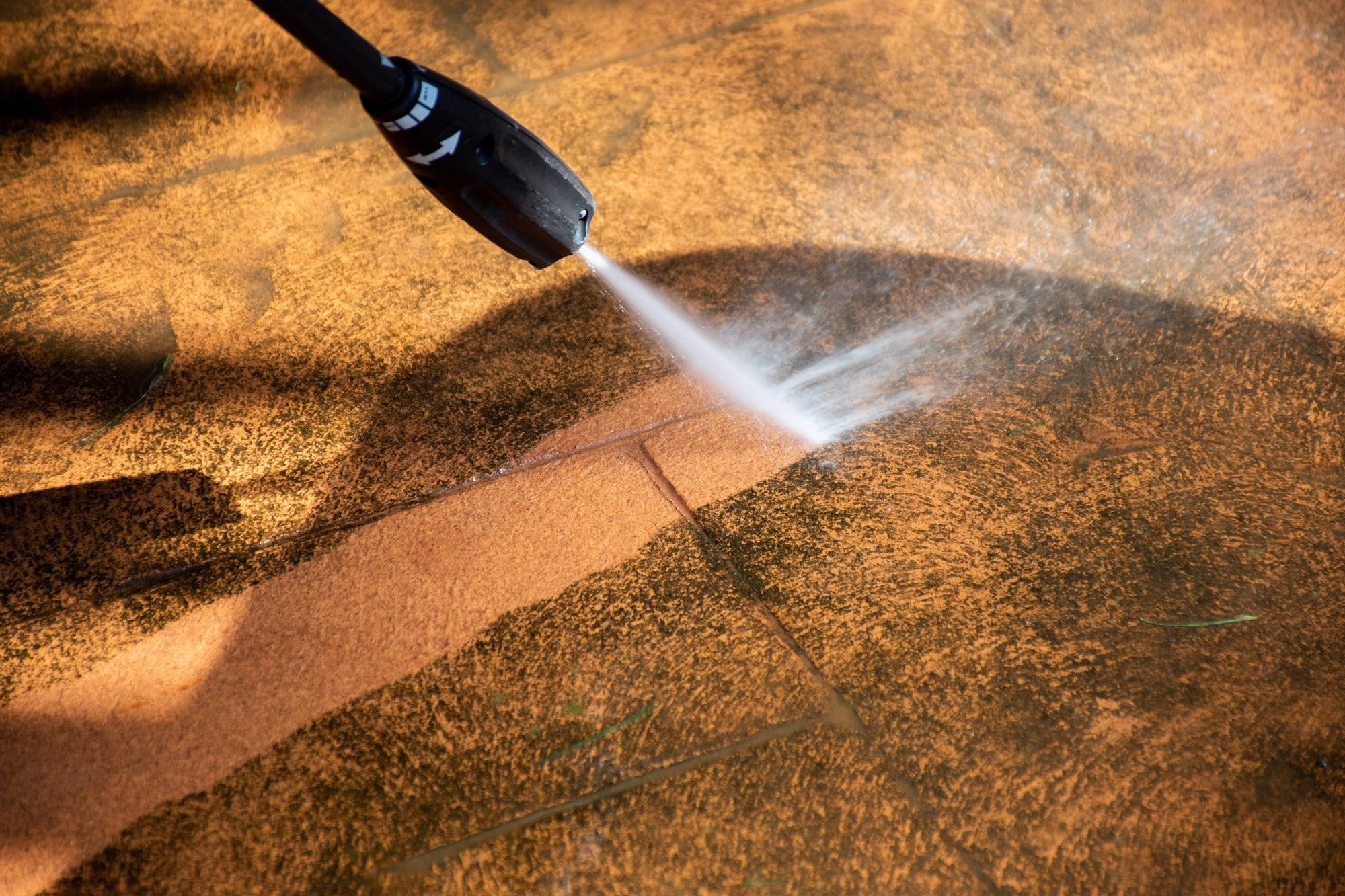 Washing the backyard tiles with high pressure cleaner